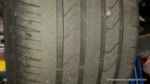 Worn out tire edge dry rot, at tread bar indicators, string plug in tire.